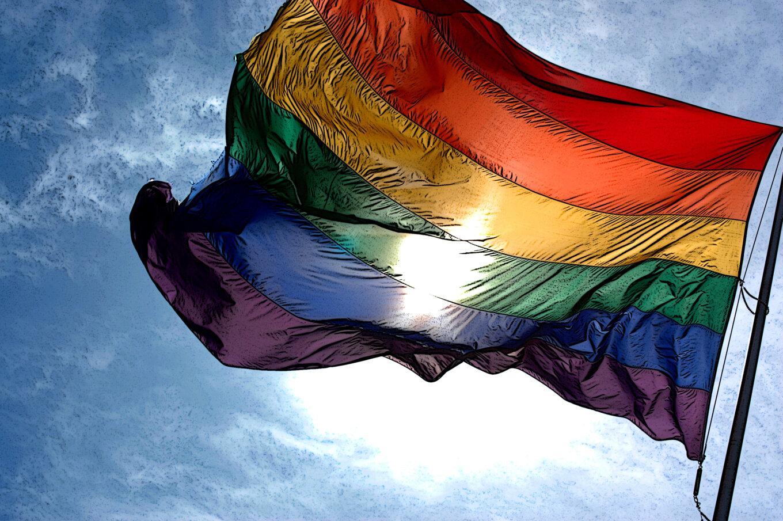 A rainbow flag against a sunny blue sky