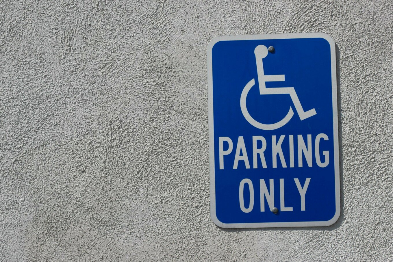 """A blue sign attached to a wall with a symbol of a wheelchair user and the words """"Parking only"""""""