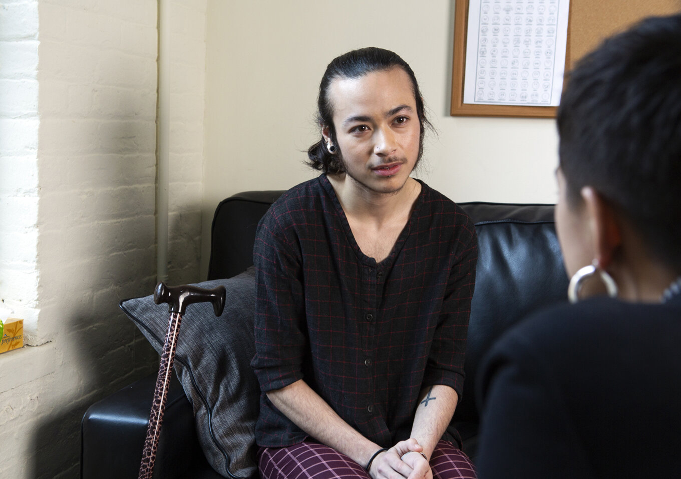 Stock photograph of a genderqueer person sitting on a therapist's couch, listening.