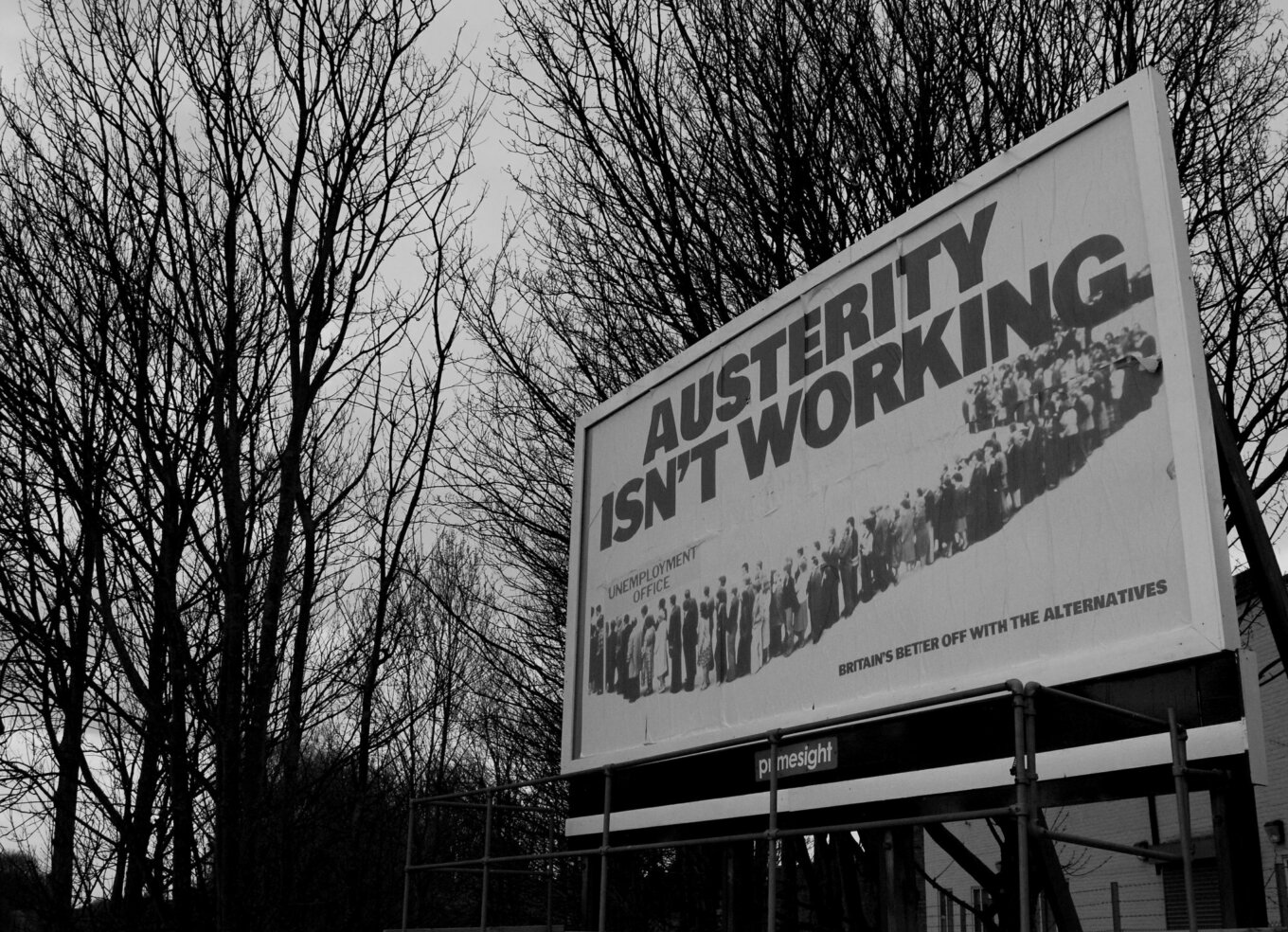A billboard with the words Austerity Isn't Working