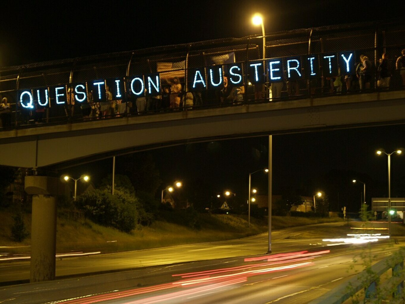 The words Question Austerity in lights on a motorway bridge
