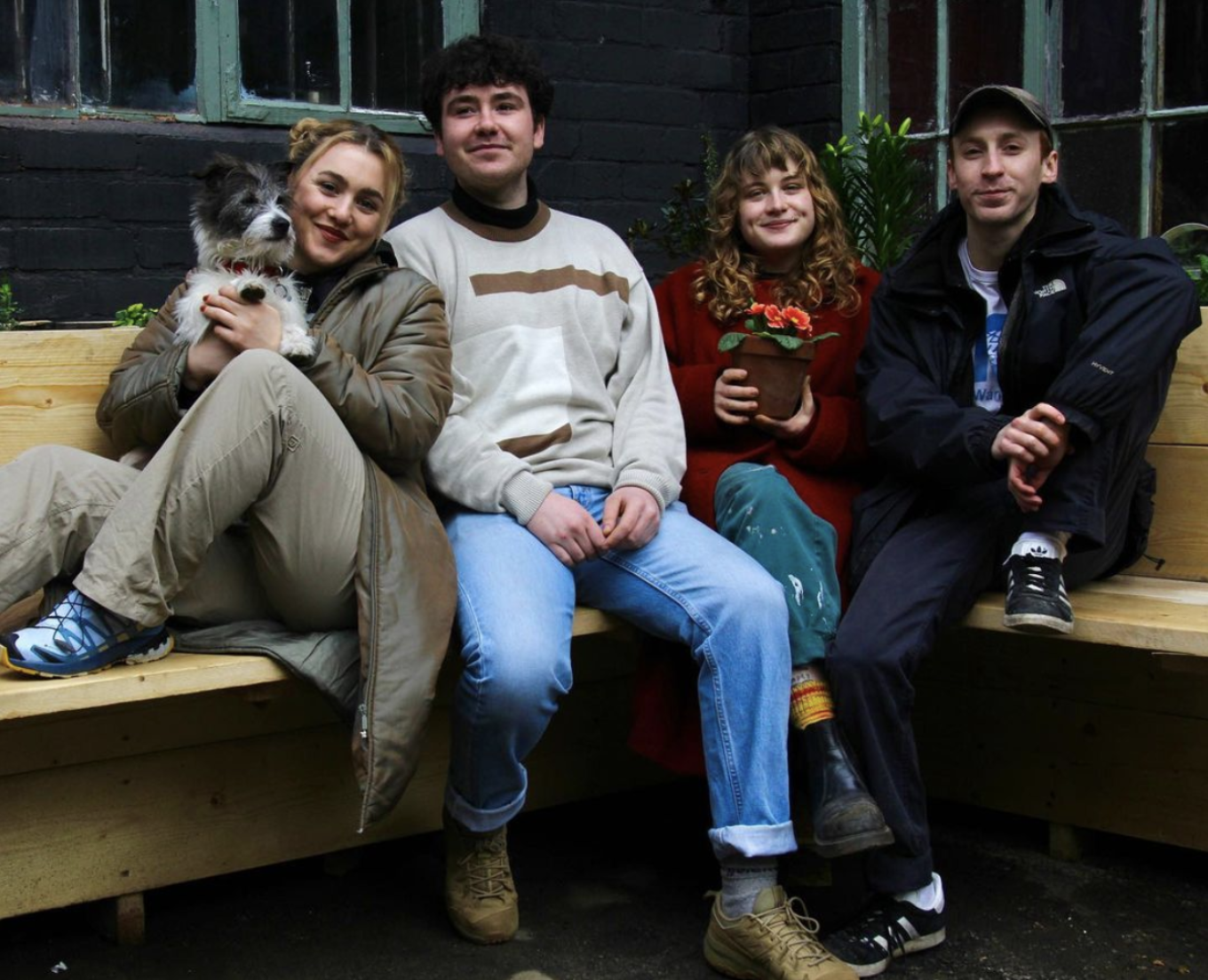 Four people sit together on a wooden corner bench, smiling into the camera, surrounded by greenery. The person on the far left holds a coarse-haired Jack Russell on their lap. The person sitting just right of holds a plant pot with bright orange flowers.