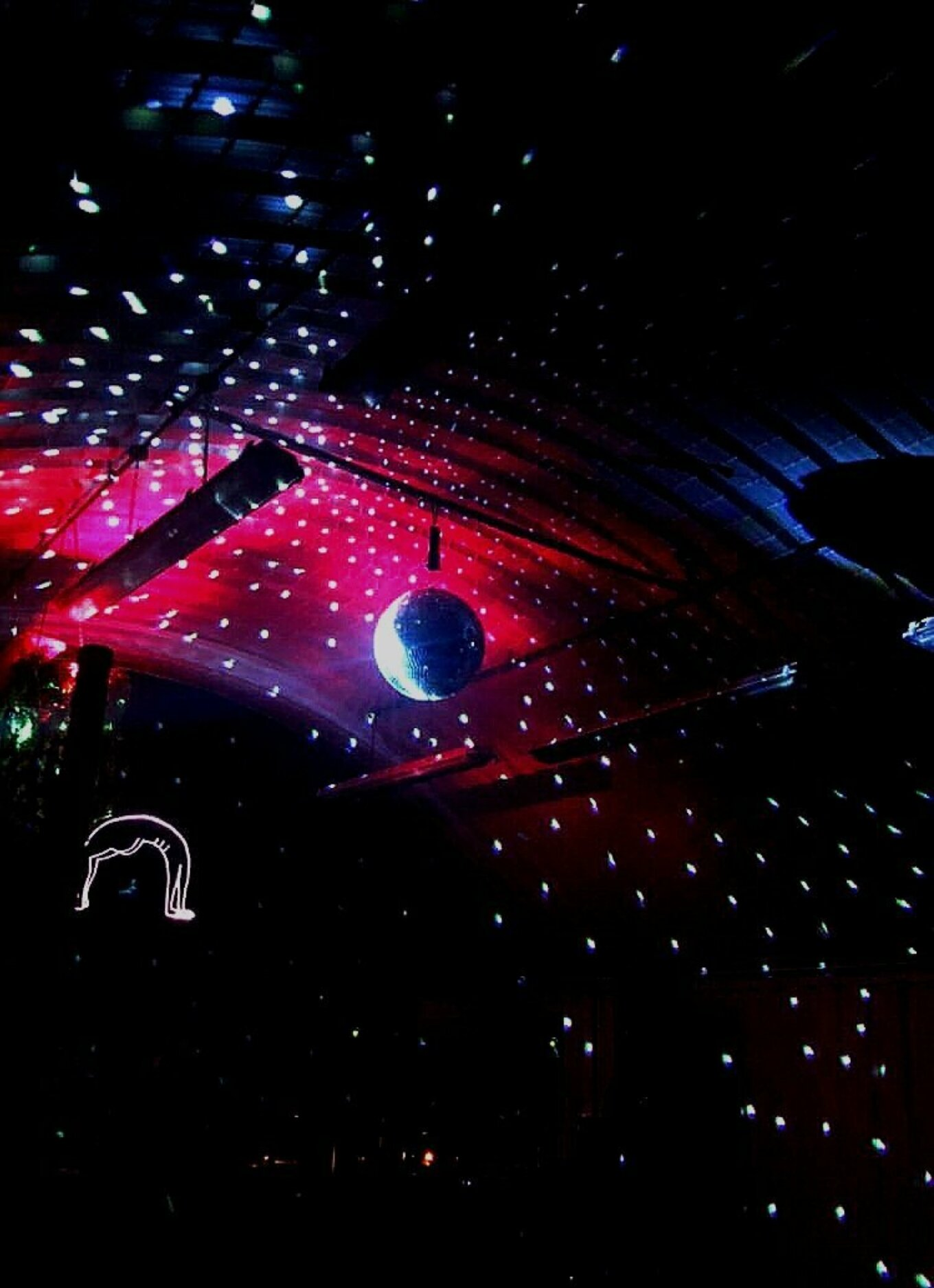 A mirror ball hangs over a darkened dancefloor. The ceiling's brickwork is lit up by pink fluorescent light and white shards of reflecting from the mirror ball.