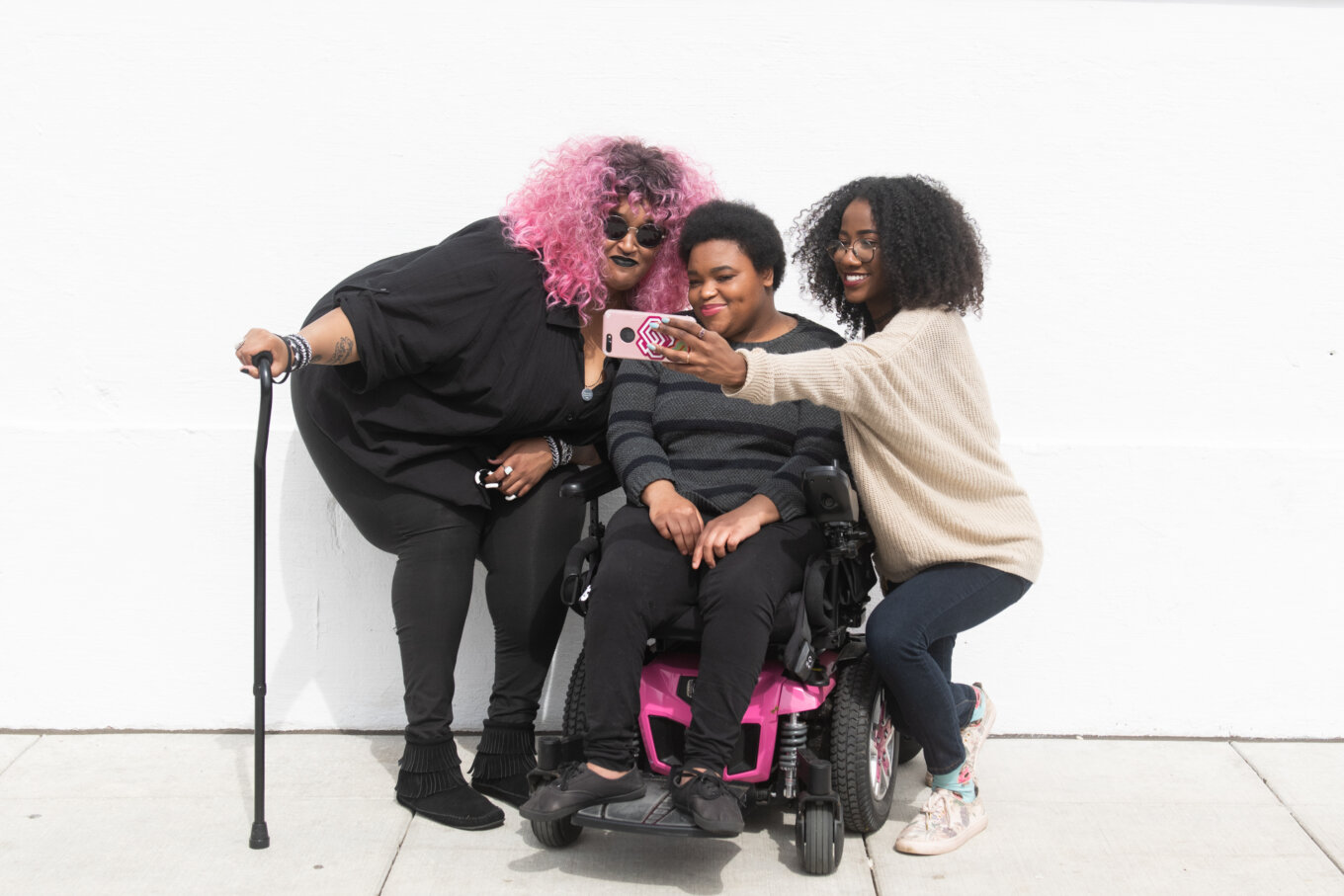 A zoomed out full body shot showing three Black and disabled friends (a non-binary person with a cane and tangle stim toy, a non-binary person sitting in a power wheelchair, and an invisibly disabled woman) smiling and taking a cell phone selfie together