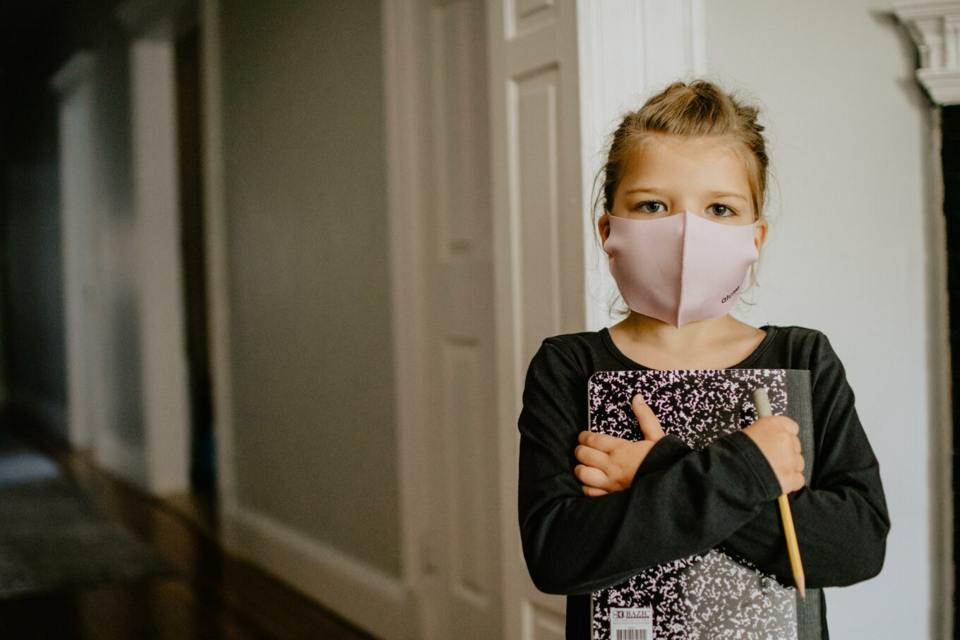 Girl with school supplies and a mask on