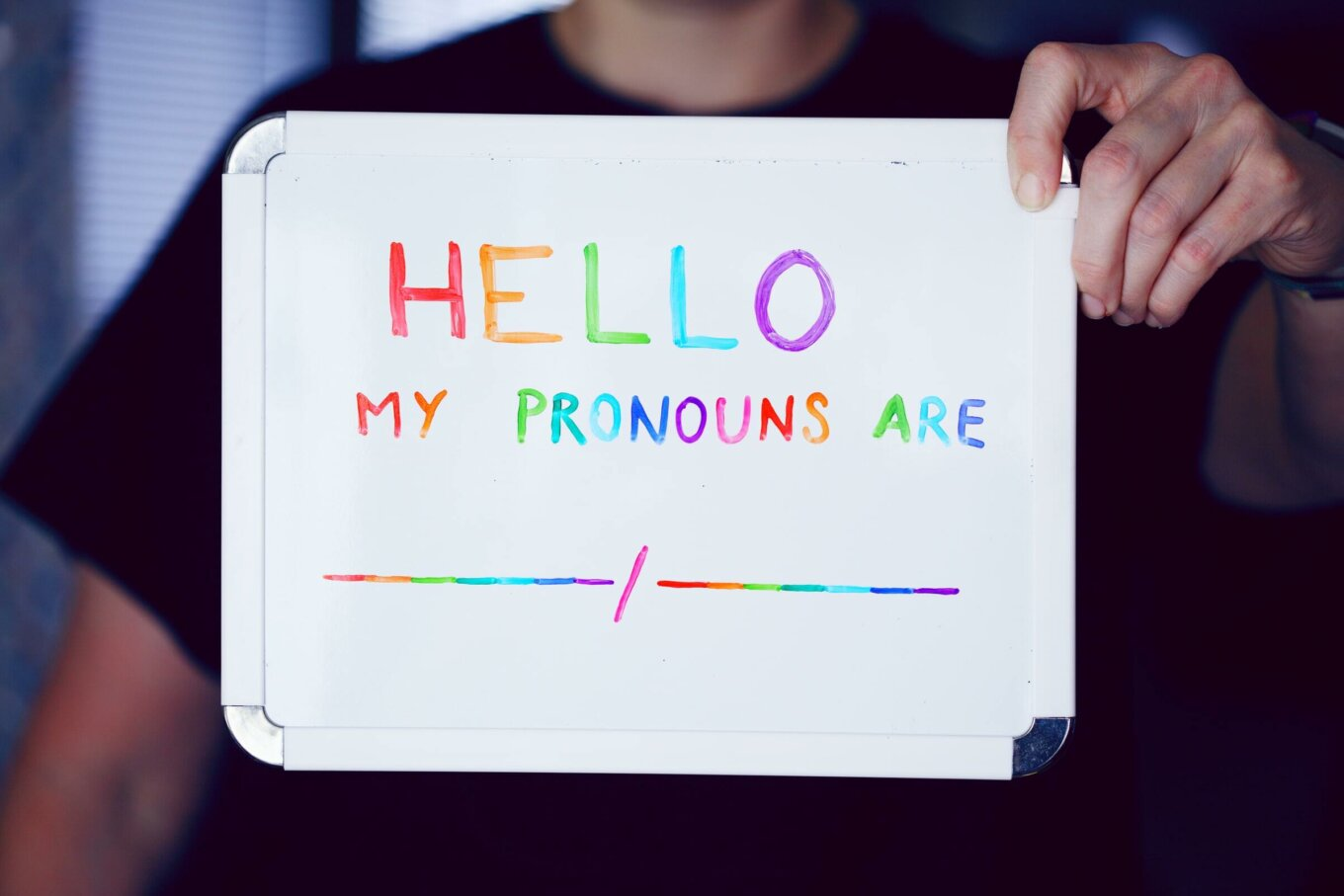 """A person holding up a whiteboard that reads """"Hello my pronouns are"""" in rainbow colours"""