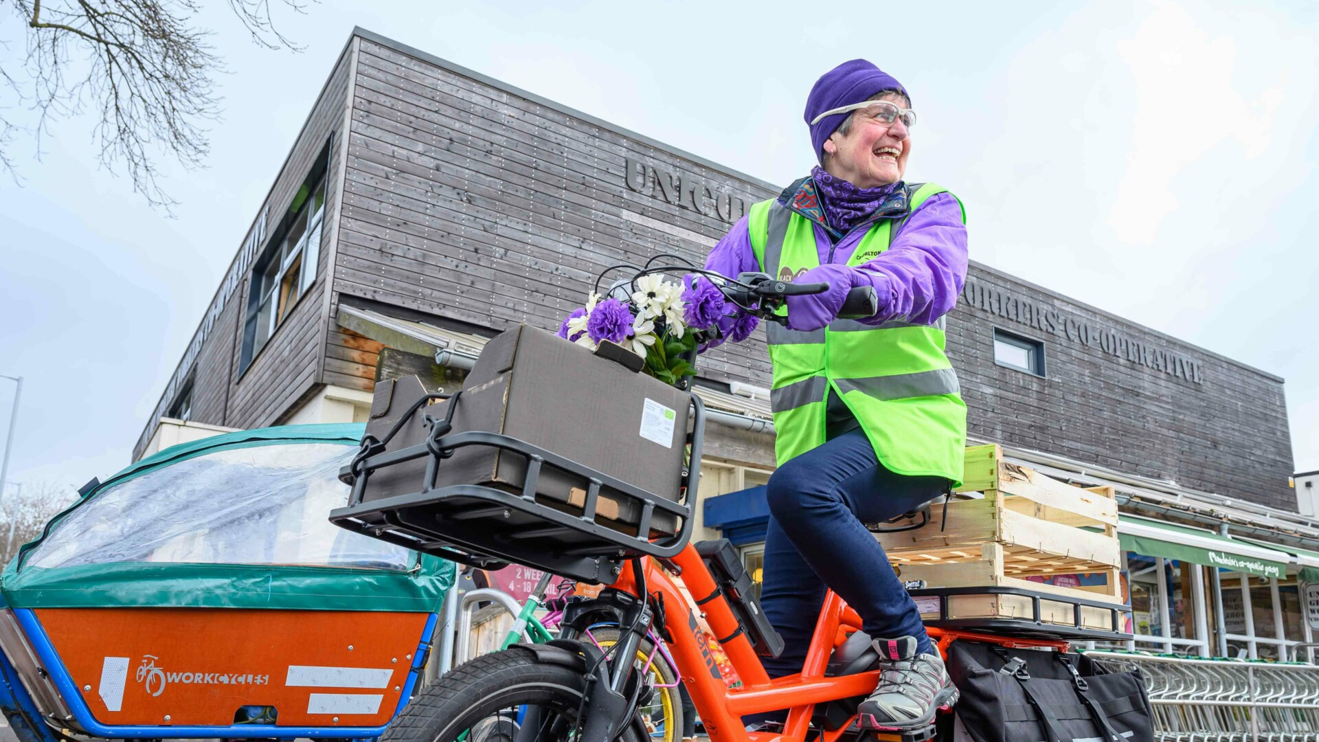 Glynis on a Chorlton Bike Deliveries cargo bike in front of Unicorn grocery store