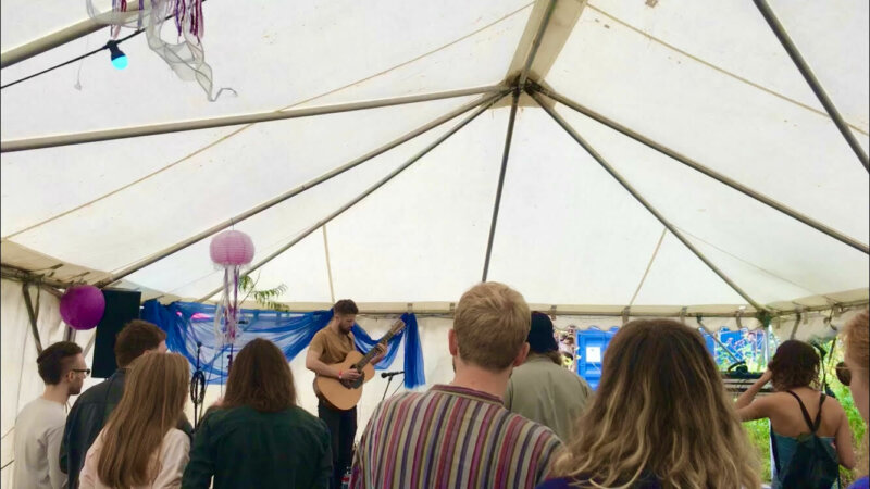George Fell performing with his acoustic guitar to open the festival