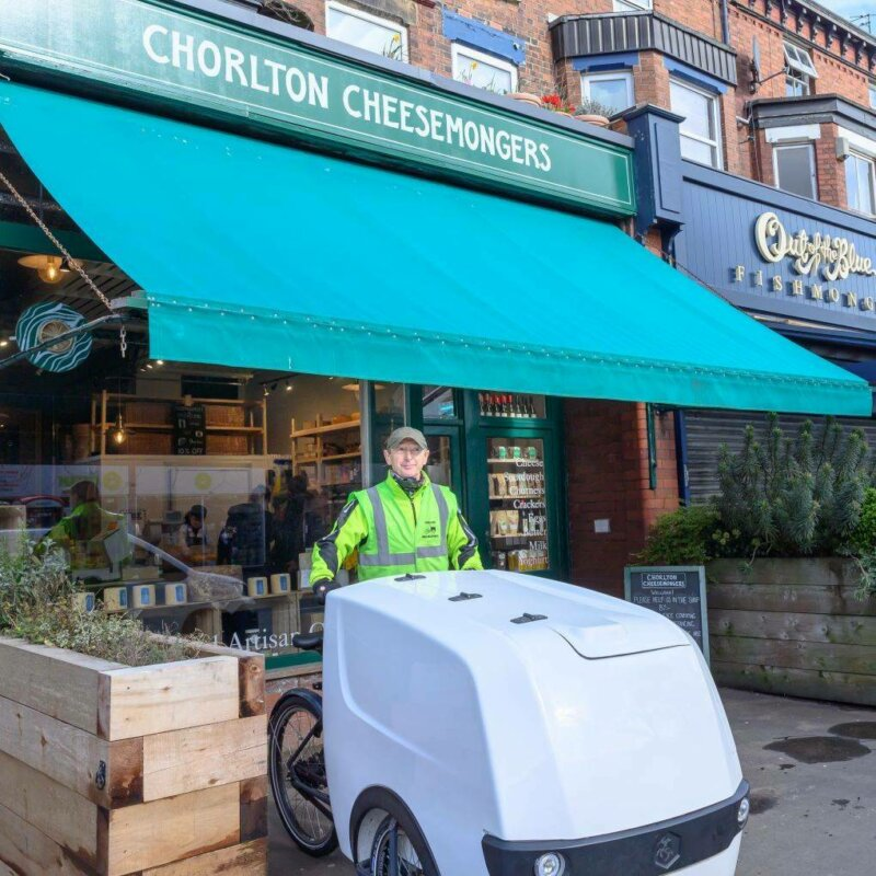 Nick from Chorlton Bike Deliveries outside Chorlton Cheesemongers with a cargo bike